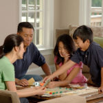 Picure of parents playing a board game with their children used for the 10 tips for running a game demo page